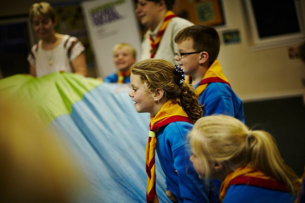 Beaver scouts playing with a parachute.