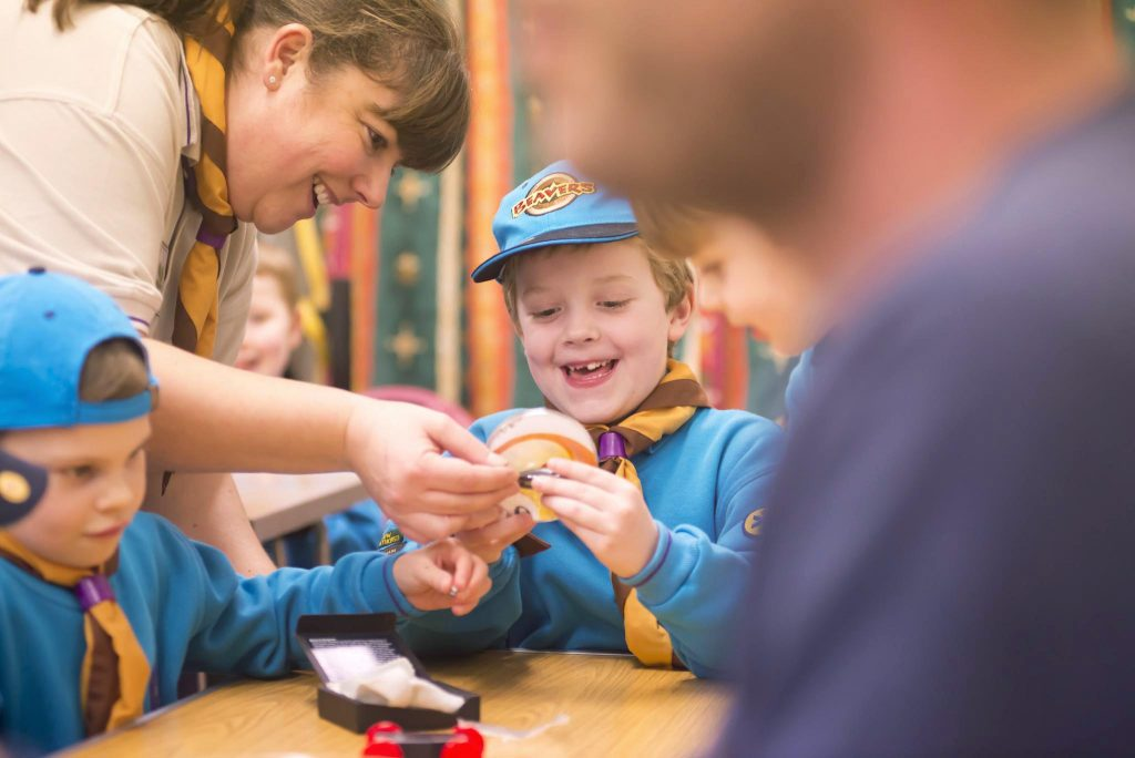 A leader helps a Beaver scout with their task.
